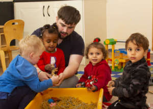 four children from the toddler room in Acorns Early Learning centre with Alan Robinson, toddler room prctitioner