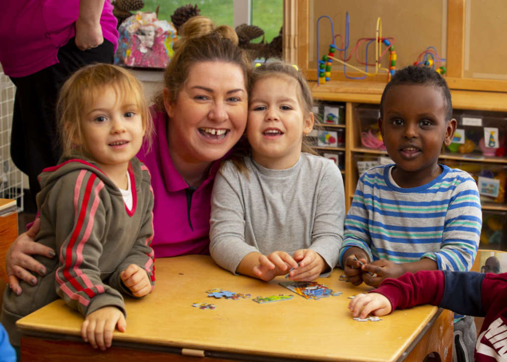 Three children and their childcare practitioner
